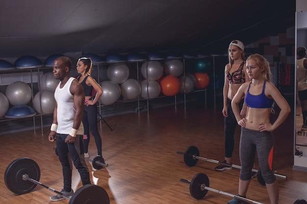 Uomo sportivo e womans preparando a fare esercizio con bilancieri. colpo orizzontale all'interno