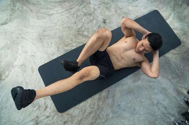 Uomo sportivo formazione facendo esercizio in palestra