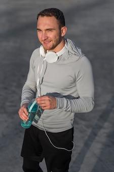 Uomo sportivo sorridente che tiene una bottiglia di acqua