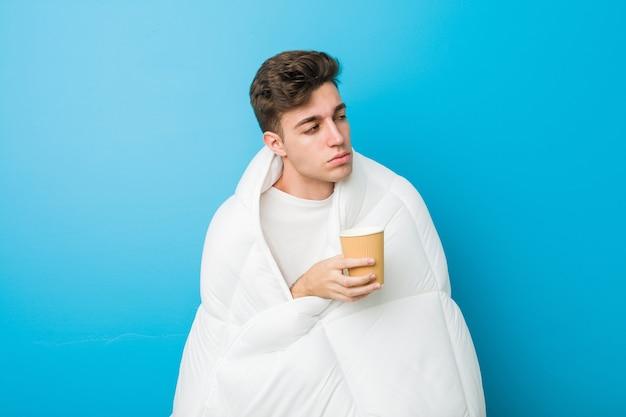 Uomo stanco caucasico dell'adolescente che si copre con una coperta e che tiene un caffè