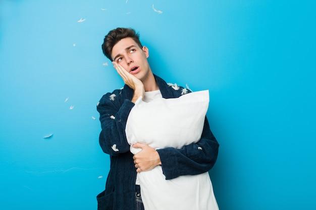 Uomo stanco caucasico dell'adolescente che tiene un cuscino