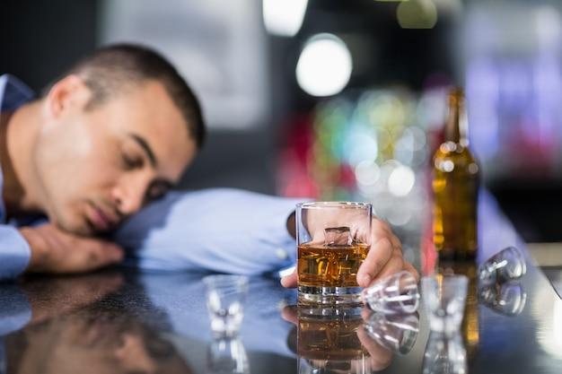 Uomo stanco che mangia un whisky e che dorme su un contatore