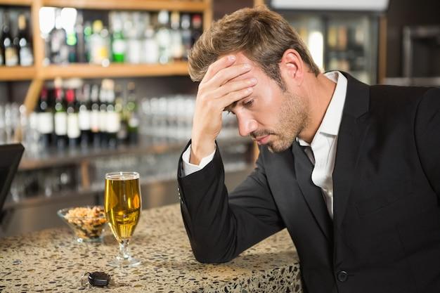 Uomo stanco che mangia una birra