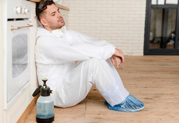 Uomo stanco della foto a figura intera sul pavimento della cucina