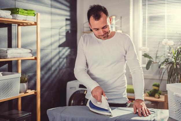 Uomo stiratura vestiti a casa