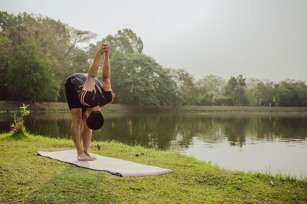 Uomo stretching, lago e natura