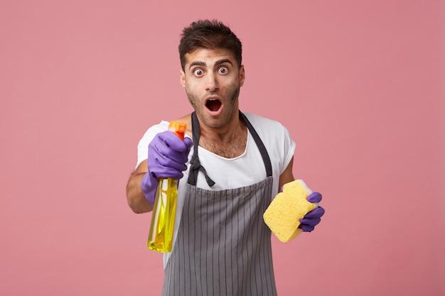 Uomo stupito con la faccia sporca che osserva con la bocca aperta e gli occhi infastiditi che tengono la spugna con il detersivo facendo la sua routine quotidiana domestica.