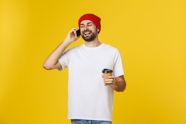 Uomo su colore giallo vibrante isolato che prende un caffè in tazza di carta asportabile e che sorride perché inizierà bene la giornata.