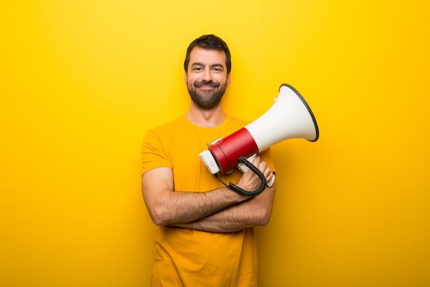 Uomo su colore giallo vibrante isolato che tiene un megafono