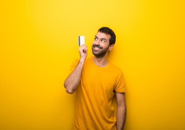 Uomo su colore giallo vibrante isolato in possesso di una carta di credito e il pensiero