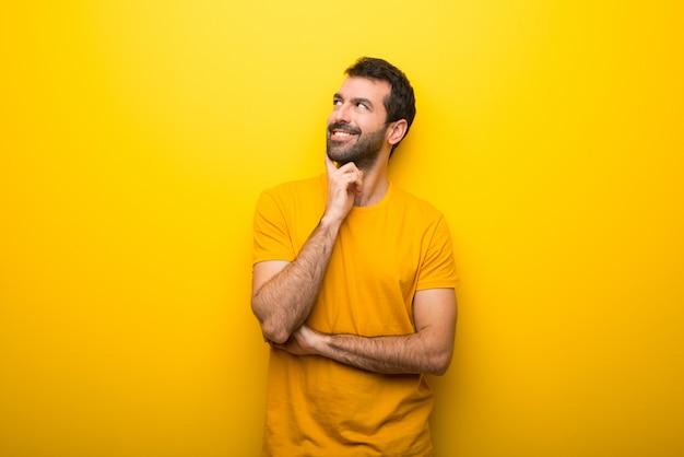 Uomo su colore giallo vibrante isolato pensando un'idea mentre alzando lo sguardo
