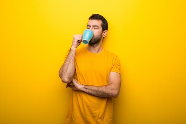 Uomo su colore giallo vibrante isolato prendendo un caffè in tazza di carta da asporto e sorridente