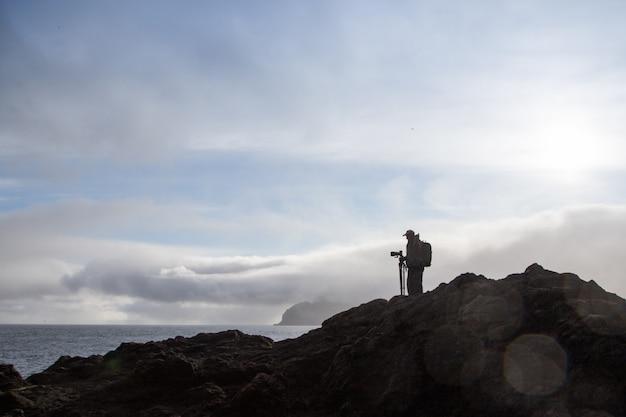 Uomo su una montagna con un treppiede e una macchina fotografica. sport e vita attiva