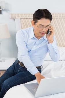 Uomo su una telefonata usando il portatile in camera da letto