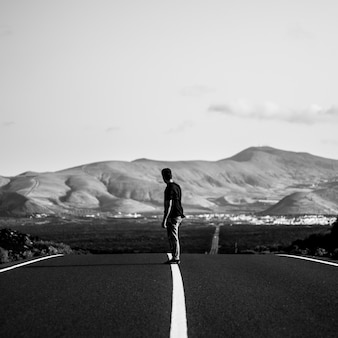 Uomo su uno skateboarder in sella su una strada statale vuota con incredibili colline
