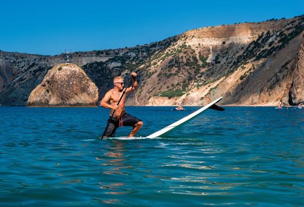 Uomo su uno stand up paddleboard sul mare