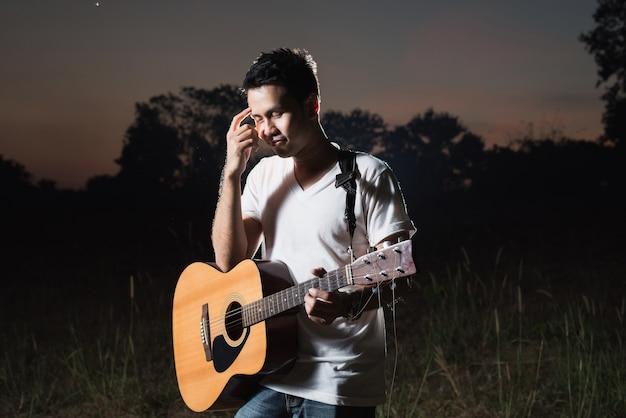 Uomo sui passi a suonare la chitarra