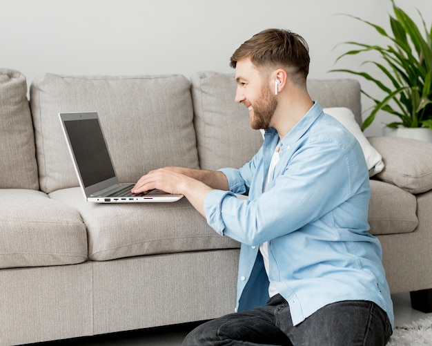 Uomo sul pavimento che lavora al computer portatile