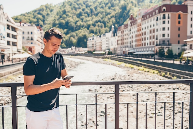 Uomo sull'argine di un fiume di montagna in una città europea.