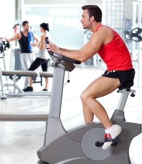 Uomo sulla bicicletta stazionaria presso la palestra di fitness sportiva