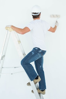 Uomo sulla pittura di scala con rullo