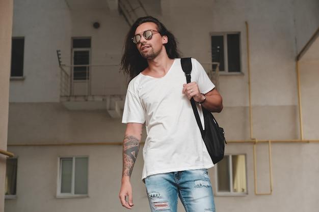 Uomo sulla scena urbana con zaino e occhiali da sole