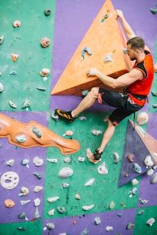 Uomo sulla sporgenza del muro di arrampicata