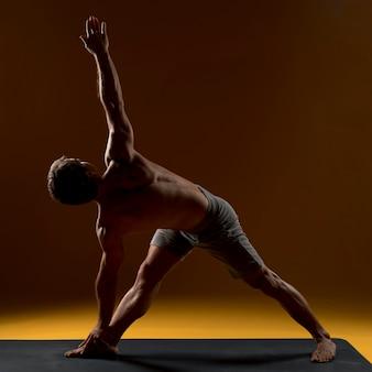 Uomo sulla stuoia di yoga che fa esercizio