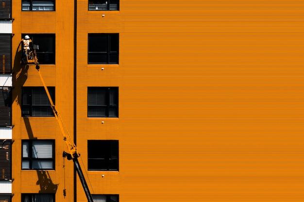Uomo sulle finestre di pulizia della gru