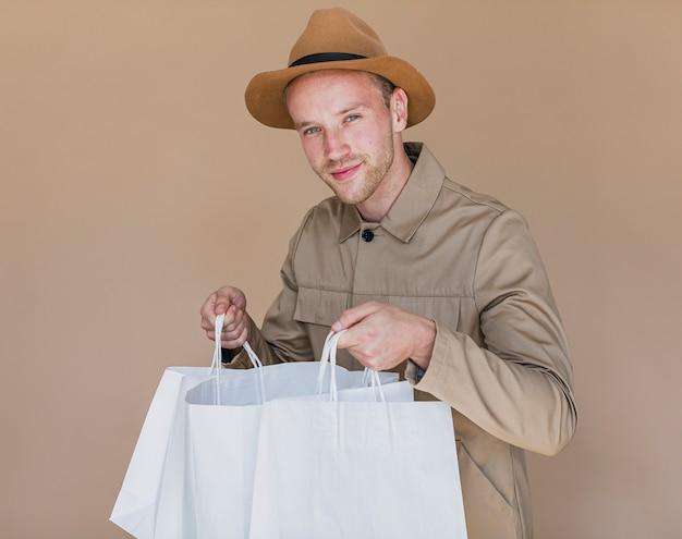 Uomo sveglio con i sacchetti della spesa che guarda alla macchina fotografica