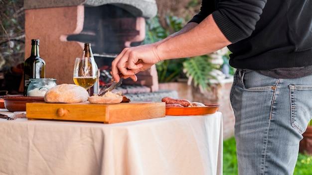 Uomo taglio pane e pollo alla griglia con forchetta e coltello all'aperto