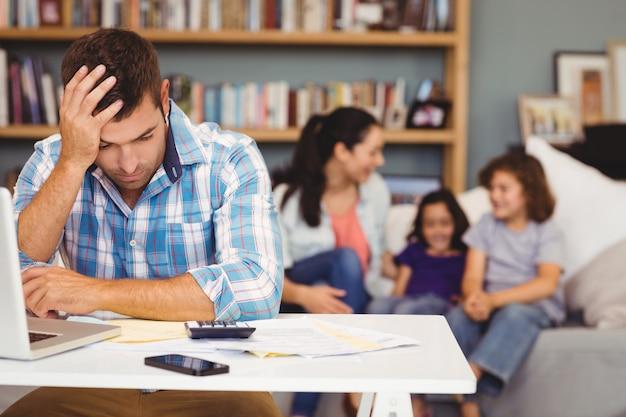 Uomo teso dal computer portatile mentre seduta della famiglia