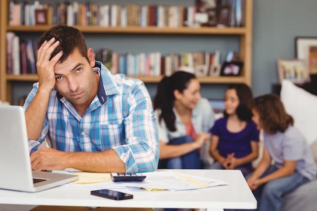 Uomo teso dalla tabella del computer portatile mentre seduta della famiglia