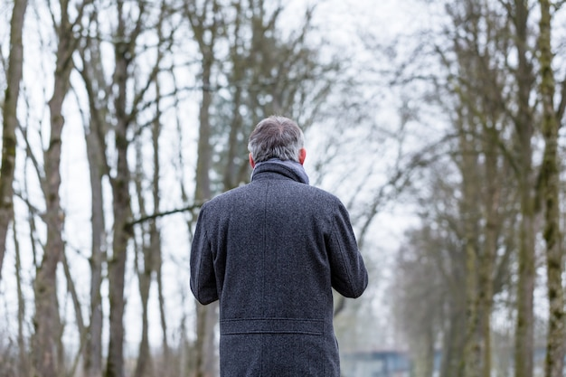 Uomo triste e solitario che cammina nel paesaggio invernale