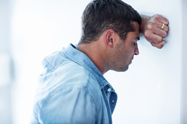 Uomo turbato che si appoggia sulla parete