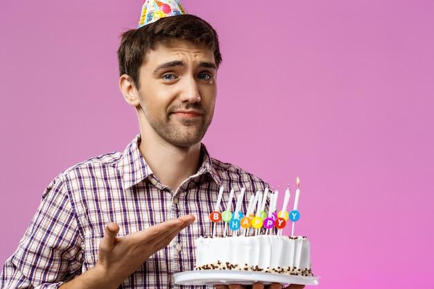 Uomo turbato che tiene la torta di compleanno con una candela non spenta.
