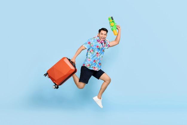 Uomo turistico asiatico bello di salto che viaggia con la pistola ad acqua e il bagaglio durante il festival di songkran