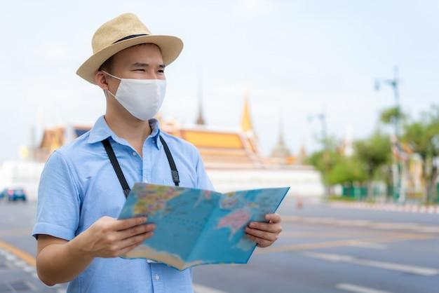 Uomo turistico asiatico che indossa una maschera protettiva