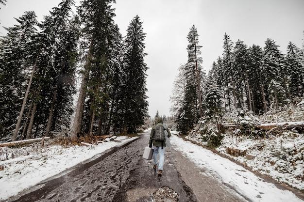 Uomo turistico con uno zaino attraversando un bosco innevato