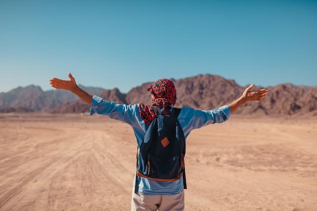 Uomo turistico con zaino sollevato le braccia sentendosi felice e libero nel deserto del sinai e montagne. paesaggio ammirante del viaggiatore