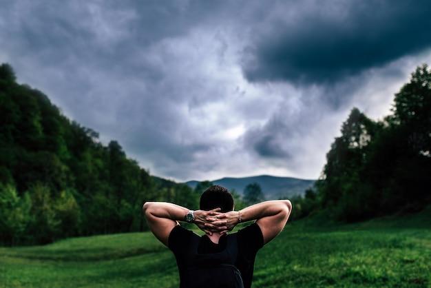 Uomo turistico in montagna con il cielo nuvoloso su sfondo