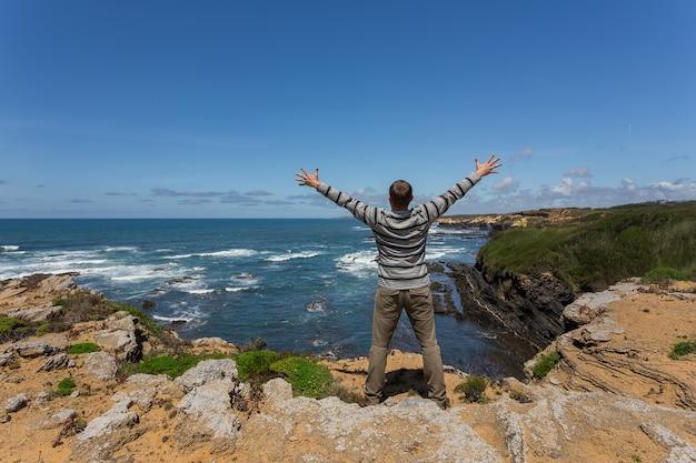 Uomo turistico sulla riva rocciosa del mare.