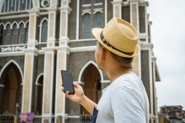 Uomo turistico tenere cellulare per scattare foto o selfie se stesso