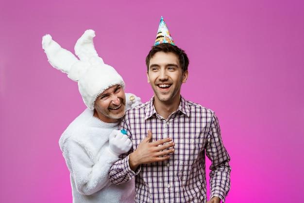 Uomo ubriaco e coniglio alla festa di compleanno sul muro viola.