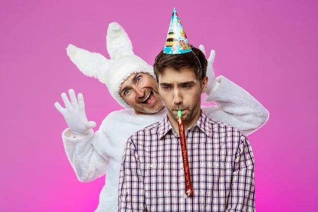 Uomo ubriaco spaventoso del coniglio sopra la parete viola. festa di compleanno.