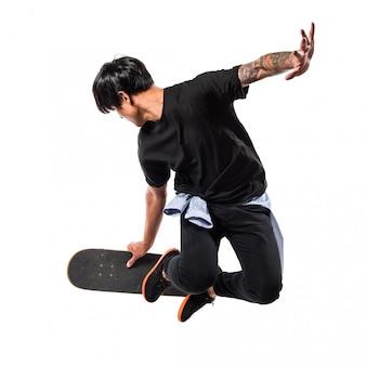 Uomo urbano asiatico che salta con il pattino
