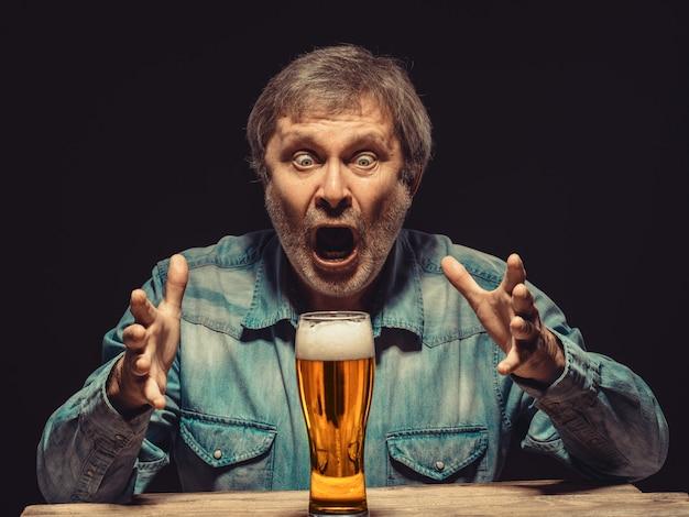Uomo urlando in camicia di jeans con un bicchiere di birra