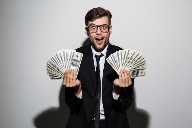 Uomo uscito felice in vetri e vestito nero che tiene due mazzi di soldi