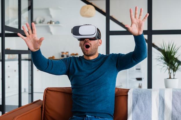 Uomo uscito sul divano con l'auricolare virtuale