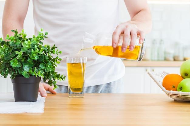 Uomo versando succo di mela dalla brocca in vetro in cucina.